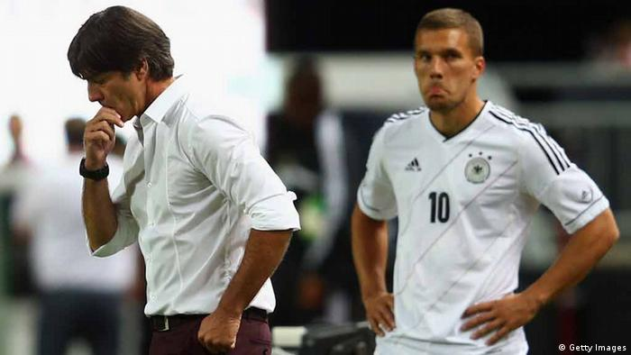 KAISERSLAUTERN, GERMANY - AUGUST 14: Head coach Joachim Loew and Lukas Podolski of Germany react during the international friendly match between Germany and Paraguay at Fritz-Walter-Stadium on August 14, 2013 in Kaiserslautern, Germany. (Photo by Alex Grimm/Bongarts/Getty Images)