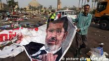 An Egyptian pulls a banner of Egypt's ousted President Mohammed Morsi near debris left at a protest camp in Nahda Square, Giza, Cairo, Egypt, Thursday, Aug. 15, 2013. Egypt faced a new phase of uncertainty on Thursday after the bloodiest day since its Arab Spring began, with over 300 people reported killed and thousands injured as police smashed two protest camps of supporters of the deposed Islamist president. Wednesday's raids touched off day-long street violence that prompted the military-backed interim leaders to impose a state of emergency and curfew, and drew widespread condemnation from the Muslim world and the West, including the United States. (AP Photo/Amr Nabil)