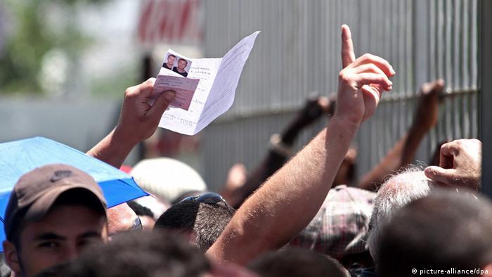 emporgereckte Hände mit Ausweisdokumenten Foto: picture-alliance/dpa
