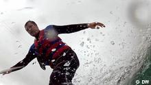 Jonas steht auf einem Wakeboard und Wasser spritzt hoch (Perspektive von unten).