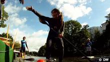 Nichole steht in Surfausrüstung mit nach vorne ausgestrecktem Arm auf dem Surfbrett