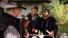 Die drei Kandidaten von Team Süd schauen auf einen Zettel, links vorne steht der Vorsitzende des Kleingartens Eberhard Baumgarten