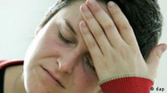 Zum Thema Kopfschmerzen: Eine Frau drückt mit den Fingern gegen die schmerzende Stirn.