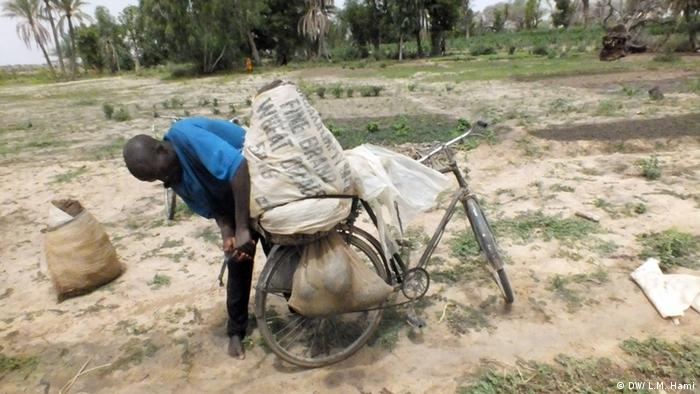 A man loads sacks on to his bicycle in a desert landscape Photo: Larwana Malam Hami (DW Korrespondent)