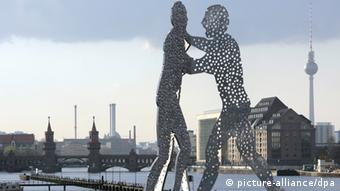 Two giant aluminum sculptures of men, with holes in their bodies Photo: picture-alliance/dpa