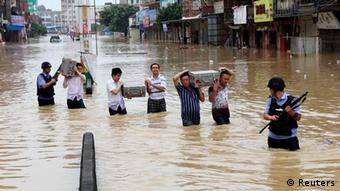 People carrying cash boxes walk across a flooded street (photo: REUTERS/Stringer)