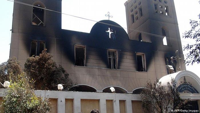 A picture taken on August 14, 2013, shows the facade of the Prince Tadros Coptic church after being torched by unknown assailants in the central Egyptian city of Minya. Egypt's Christians are living in fear after a string of attacks against churches, businesses and homes they say were carried out by angry supporters of ousted Islamist president Mohamed Morsi. AFP PHOTO/STR (Photo credit should read -/AFP/Getty Images)