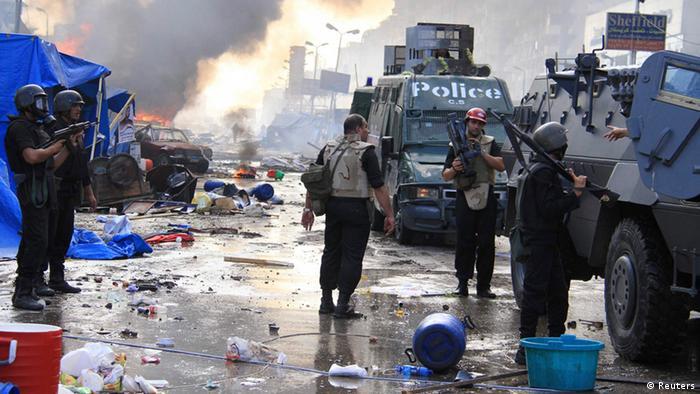 Ein Fernsehteam steht neben Panzern und Angehörigen des Militärs während im Hintergrund Feuer und zerstörte Straßen nach einem Zusammenprall zwischen der Polizei und Pro-Muris-Demonstranten zu sehen sind (Foto: REUTERS)