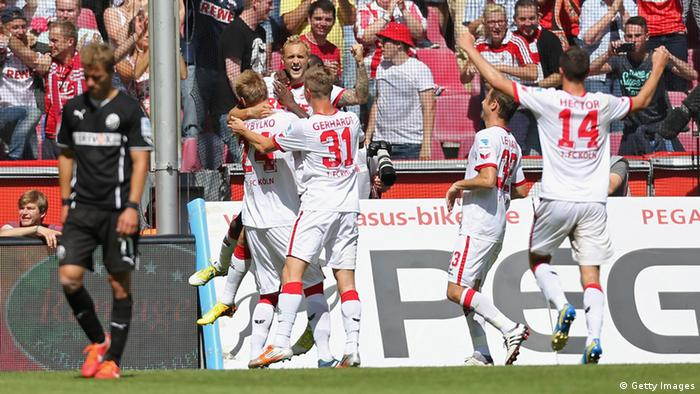 COLOGNE, GERMANY - AUGUST 17: Marcel Risse of Cologne is hugged by team-mates after scoringtheir second goal from the penalty spot during the Second Bundesliga match between 1. FC Koeln and SV Sandhausen on August 17, 2013 in Cologne, Germany. (Photo by Juergen Schwarz/Bongarts/Getty Images)