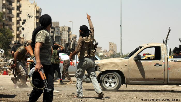 A Syrian rebel points to the sky as a regime fighter jet flies overhead in Syria's eastern town of Deir Ezzor, on August 17, 2013. Al-Qaeda loyalists attacked a mainly Kurdish town in northeastern Syria sparking fighting in which 17 people were killed, two of them ambulance crew, a watchdog said. AFP PHOTO/ABO SHUJA (Photo credit should read ABO SHUJA/AFP/Getty Images)