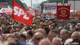BERLIN, GERMANY - AUGUST 17: Supporters of the German Social Democrats (SPD) listen to a speech by SPD chancellor candidate Peer Steinbrueck at the Deutschland Fest marking the 150th anniversary of the SPD on August 17, 2013 in Berlin, Germany. Steinbrueck is trailing incumbent Chancellor Angela Merkel and the German Christian Democrats (CDU) significantly ahead of federal elections scheduled for September 22. (Photo by Sean Gallup/Getty Images)