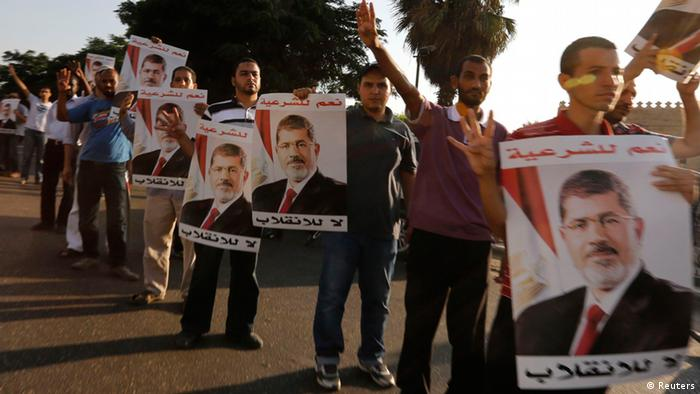 Supporters of deposed Egyptian President Mohamed Mursi hold up posters of him during a protest along Zahara street in Cairo August 18, 2013. REUTERS/Louafi Larbi