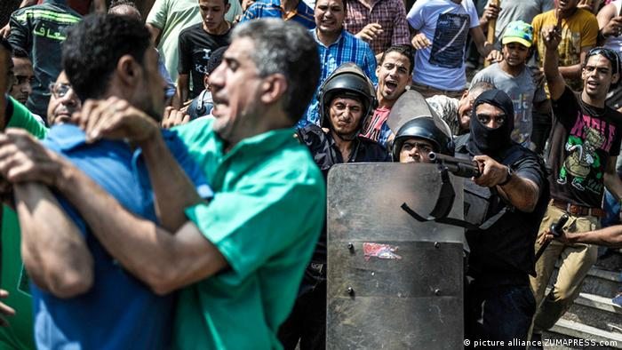 Aug. 17, 2013 - Cairo, Egypt - Egyptians security forces escort an Islamist supporter of the Muslim Brotherhood out of the al-Fatah mosque through angry crowds, in downtown Cairo, Egypt, on August 17, 2013...Photo: Mohamed Mahmoud/NurPhoto
