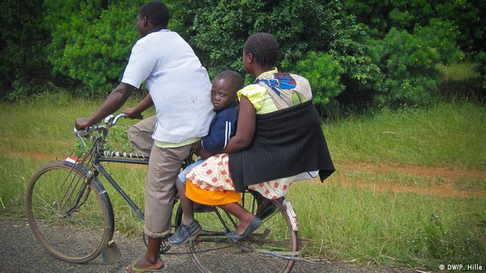 A Malawian man rides a bicycle with his wife and son on the back