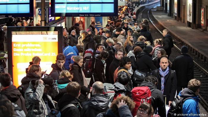 Menschen stehen dicht gedrängt auf einem Bahnsteig.