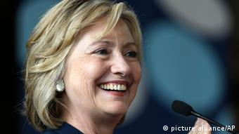 Hillary Clinton smiles off-camera while speaking into a small black microphone. Photo: Matt Rourke