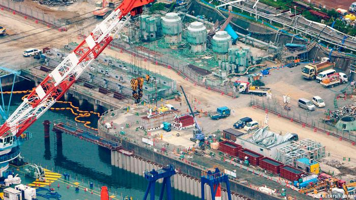 An aerial view shows workers wearing protective suits and masks work at a construction site (C) of the shore barrier to stop radioactive water from leaking into the sea, at the tsunami-crippled Fukushima Daiichi nuclear power plant in Fukushima, in this photo taken by Kyodo August 9, 2013. Highly radioactive water from Japan's crippled Fukushima nuclear plant is pouring out at a rate of 300 tons a day, officials said on Wednesday, as Prime Minister Shinzo Abe ordered the government to step in and help in the clean-up. The revelation amounted to an acknowledgement that plant operator Tokyo Electric Power Co (Tepco) has yet to come to grips with the scale of the catastrophe, 2 1/2 years after the plant was hit by a huge earthquake and tsunami. Tepco only recently admitted water had leaked at all. Mandatory Credit. REUTERS/Kyodo (JAPAN - Tags: DISASTER ENVIRONMENT POLITICS) ATTENTION EDITORS - THIS IMAGE HAS BEEN SUPPLIED BY A THIRD PARTY. IT IS DISTRIBUTED, EXACTLY AS RECEIVED BY REUTERS, AS A SERVICE TO CLIENTS. FOR EDITORIAL USE ONLY. NOT FOR SALE FOR MARKETING OR ADVERTISING CAMPAIGNS. MANDATORY CREDIT. JAPAN OUT. NO COMMERCIAL OR EDITORIAL SALES IN JAPAN. YES