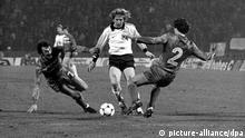 Der ballführende deutsche Mittelfeldspieler Bernd Schuster (M) wird von zwei belgischen Gegenspielern angegriffen. Die deutsche Fußballnationalmannschaft gewinnt am 29.02.1984 im Brüsseler Heysel-Stadion das Länderspiel gegen Belgien mit 1:0.