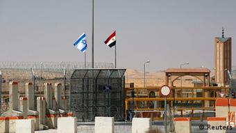 An Israeli flag (L) flutters next to an Egyptian one at the Nitzana crossing, along Israel's border with Egypt's Sinai desert. REUTERS/Ronen Zvulun (ISRAEL - Tags: POLITICS)