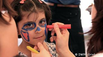 A young girl sitting in a chair has make-up applied to her face with magic markers by a woman whose face is off-camera. (Photo: Monika Griebeler / DW)