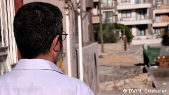 A middle-aged Syrian man looks away from the camera and at some Turkish housing complexes. (Photo: Monika Griebeler / DW))