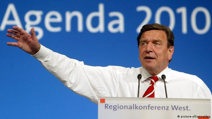 Former German Chancellor Gerhard Schröder stands before a sign that reads Agenda 2010 (photo: picture alliance)