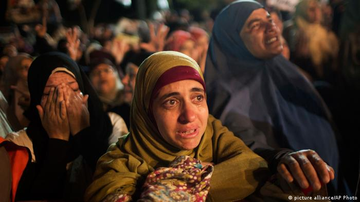 A supporter of Egypt's ousted President Mohammed Morsi cries during a fake funeral in tribute to colleagues killed on Saturday during a clash, at Nasr City, where protesters have installed a camp and hold daily rallies, in Cairo, Egypt, Monday, July 29, 2013. (AP Photo/Manu Brabo) pixel