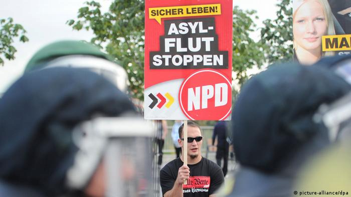 An NPD protester holding a sign in Berlin district of Hellersdorf (c) picture-alliance/DPA