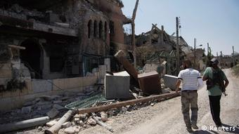 Free Syrian Army fighters walk past damaged buildings and debris in Deir al-Zor August 20, 2013. Picture taken August 20, 2013. REUTERS/Khalil Ashawi (SYRIA - Tags: CONFLICT POLITICS CIVIL UNREST)