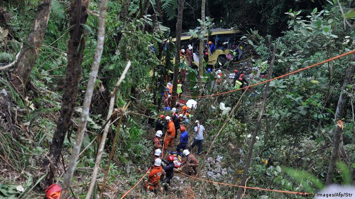 Malaysian emergency services personnel work to rescue passengers after a bus (C-top) carrying tourists and local residents fell into a ravine near the Genting Highlands, about an hour's drive from Kuala Lumpur on August 21, 2013. AFP PHOTO