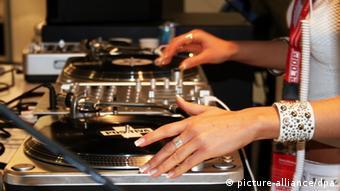 Eine junge Frau legt auf der Musikmesse Platten auf.