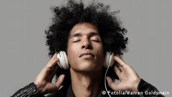 Ein Mann hat einen Kopfhörer auf den Ohren und hört verzückt mit geschlossenen Augen zu