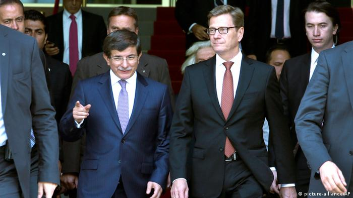 German Foreign Minister Guido Westerwelle, right, and his counterpart from Turkey, Ahmet Davutoglu, left, leave the foreign office after a meeting in Berlin, Germany, Thursday, Aug. 22, 2013. (AP Photo/Michael Sohn)
