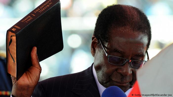 Zimbabwean President Robert Mugabe, holding up a Bible, is sworn in during his inauguration ceremony in Harare on August 22, 2013 Photo: ALEXANDER JOE/AFP/Getty Images