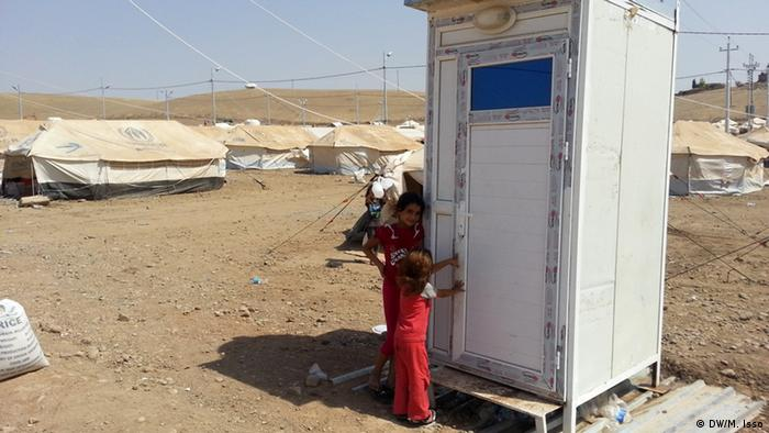 A Syrian girl outside a white mobile toilet. (Photo: Mihyedin Isso)