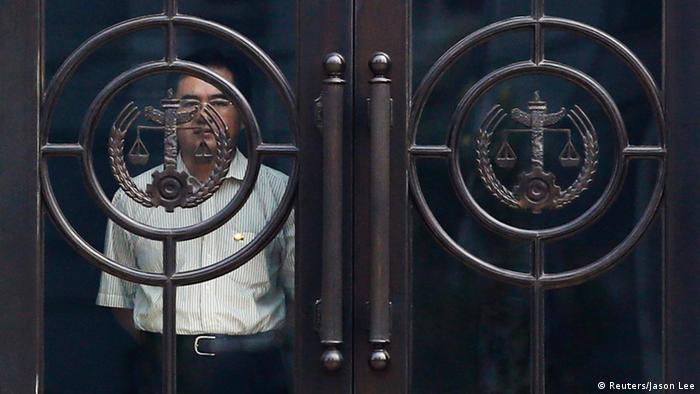 A man looks out behind the door of the Jinan Intermediate People's Court building during the trial of disgraced Chinese politician Bo Xilai in Jinan, Shandong province August 23, 2013. China's state media called Bo, the former Communist Party chief of the Chongqing region, arrogant and a liar for his robust defence at his landmark trial, the country's highest profile court case since the Gang of Four was dethroned in the 1970s and put in the dock. REUTERS/Jason Lee (CHINA - Tags: POLITICS CRIME LAW CIVIL UNREST SOCIETY)