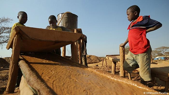 Two 13-year-old boys and one 15-year-old boy pour crushed gold ore over a sisal sack to concentrate the particles of gold at a processing site in Mbeya Reigon, Tanzania. PHOTO: Justin Purefoy for Human Rights Watch.