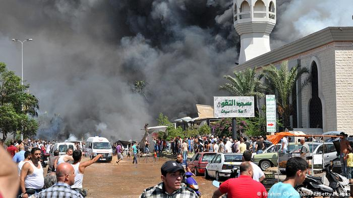 Smoke is seen above people gathering outside a mosque on the site of a powerful explosion in the northern Lebanese city of Tripoli on August 23, 2013. Two powerful explosions killed several people: one rocked the city centre near the home of outgoing Prime Minister Najib Mikati, the second one struck near the port of the restive city with a Sunni Muslim majority. The explosions come a week after a suicide car bombing killed 27 people in a Beirut stronghold of the Lebanese Shiite movement Hezbollah, which is fighting alongside Assad's forces. AFP PHOTO IBRAHIM CHALHOUB (Photo credit should read IBRAHIM CHALHOUB/AFP/Getty Images)