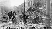 Dieser Aufstand ist nicht mit dem vorausgegangenen Aufstand im Warschauer Ghetto des Jahres 1943 zu verwechseln! Der Aufstand in Warschau niedergeschlagen. Wie das Oberkommando der Wehrmacht am Dienstag mitteilte, ist die Aufstandsbewegung in Warschau nunmehr völlig zusammengebrochen. Nach wochenlangen Kämpfen, die zur völligen Zerstörung der Stadt führten, haben die Reste der Auständigen, von allen ihren Verbündeten verlassen, den Widerstand eingestellt und kapituliert. - Hinter Barrikaden aus Pflastersteinen, Hausrat und Fahrzeugen aller Art versuchten die Aufständigen, den Ansturm unserer Truppen aufzuhalten, bis der versprochene Durchstoss sowjetischer Divisionen sie befreien sollte. Aber die sowjetische Hilfe blieb aus und so wurde der Aufstand durch den harten Zugriff unsererr Soldaten nach schweren Kämpfen zerschlagen. Unser Bild zeigt: Grenadiere haben eine von den Aufständigen verteidigte Barrikade genommen und stossen nun weiter vor. SS-PK-Kriegsberichter Schremmer (Sch) 5.10.44 [Herausgabedatum] Description Information added by Wikimedia users. English: Warsaw Uprising: Germans on Focha Street (now called Molier Street) attack towards Town Hall and Blanka Palace Polski: Powstanie Warszawskie: Niemcy na ulicy Focha (teraz Moliera) natarcie w kierunku Ratusza i Pałacu Blanka. Z tyłu widać nowe skrzydło biurowe Ratusza. Depicted place Warsaw Uprising Date 1944-09 Photographer Schremmer Institution German Federal ArchivesLink back to Institution infobox template wikidata:Q685753 Allgemeiner Deutscher Nachrichtendienst - Zentralbild (Bild 183) Accession number Bild 183-J27793 Source Logo Bundesarchiv This image was provided to Wikimedia Commons by the German Federal Archive (Deutsches Bundesarchiv) as part of a cooperation project. The German Federal Archive guarantees an authentic representation only using the originals (negative and/or positive), resp. the digitalization of the originals as provided by the Digital Image Archive.