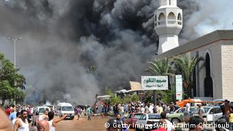 Smoke is seen above people gathering outside a mosque on the site of a powerful explosion in the northern Lebanese city of Tripoli (photo: IBRAHIM CHALHOUB/AFP/Getty Images)