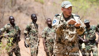 A Bundeswehr instructor is training Malian soldiers in the field