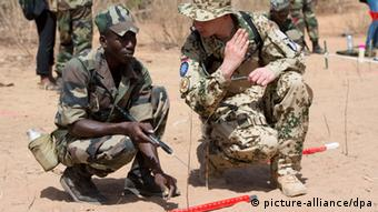 A German military trainer giving instructions to a Malian soldier