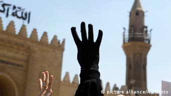 A black-gloved hand with four fingers extended is held up against the backdrop of a Caro mosque. (Photo: AP Photo/Amr Nabil)