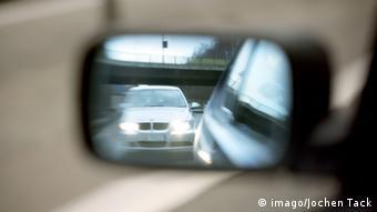 Ein Auto ist im Außenspiegel eines anderen Fahrzeugs sichtbar.