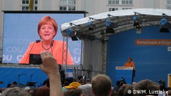 Angela Merkel speaks at a campaign event, flanked by a large monitor showing her face Copyright: DW/Marcus Lütticke