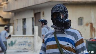 An activist wearing a gas mask is seen in the Zamalka area, where activists say chemical weapons were used by forces loyal to President Bashar Al-Assad in the eastern suburbs of Damascus August 22, 2013. REUTERS/Bassam Khabieh