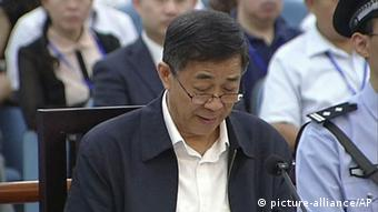 In this image taken from video, Former Chinese politician Bo Xilai reads in a court room at Jinan Intermediate People's Court in Jinan, eastern China's Shandong province, Sunday, Aug. 25, 2013. (AP Photo/CCTV via AP Video)