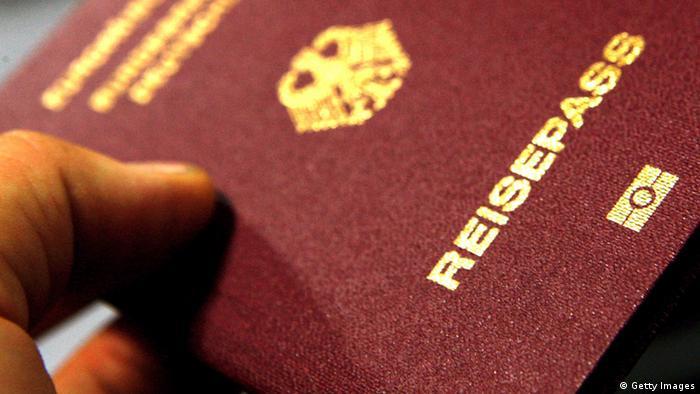 A man's hand holds a German passport
