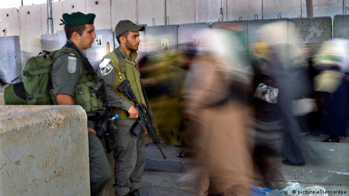 Palestinians walking past Israeli soldiers at a checkpoint in Kalandia