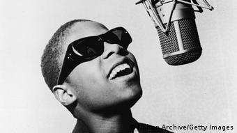Popular American musician and singer Stevie Wonder smiles and sings into a microphone in a recording studio in this early promotional photo, 1963. Copyright: Hulton Archive/Getty Images